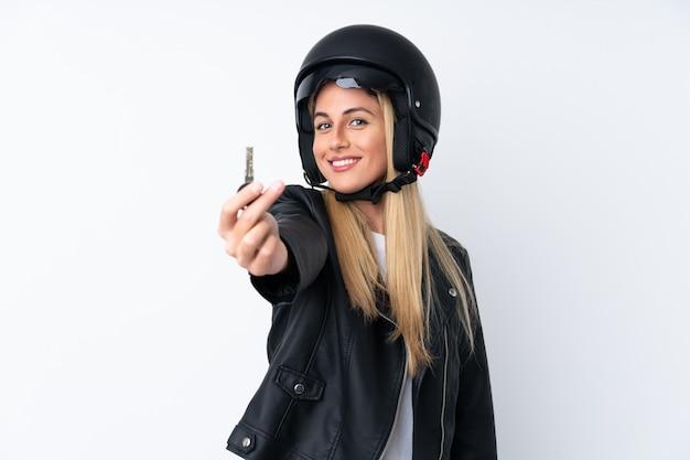 Giovane donna uruguaiana con un casco del motociclo sopra la parete bianca isolata