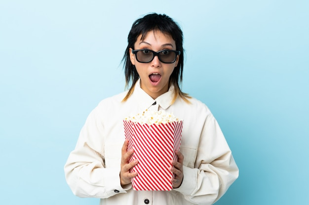 Giovane donna uruguaiana sopra isolato blu sorpreso con gli occhiali 3d e in possesso di un grande secchio di popcorn