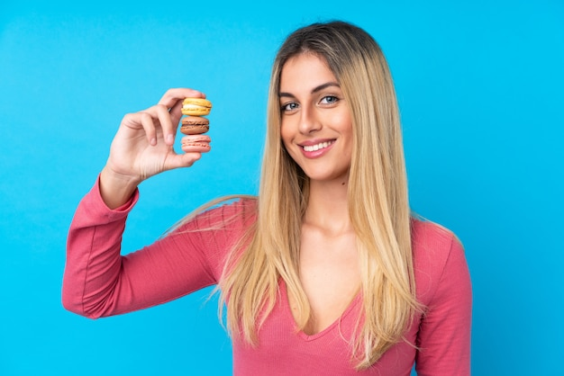 Giovane donna uruguaiana sopra la parete blu isolata che tiene i macarons francesi variopinti e che sorride molto