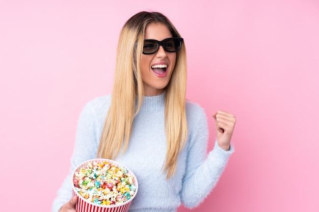 Giovane donna uruguaiana sopra la parete rosa isolata con gli occhiali 3d e in possesso di un grande secchio di popcorn