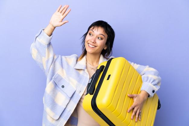 Giovane donna uruguaiana sul muro viola in vacanza con valigia viaggio e saluto
