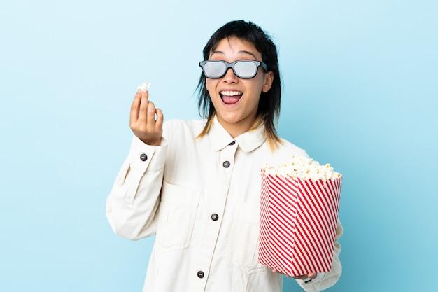 Giovane donna uruguaiana sulla parete blu con gli occhiali 3d e in possesso di un grande secchio di popcorn