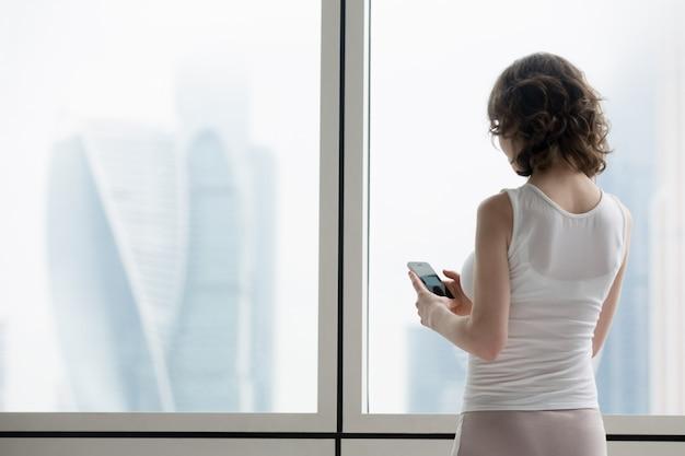 Giovane, donna, usando, smartphone, interno