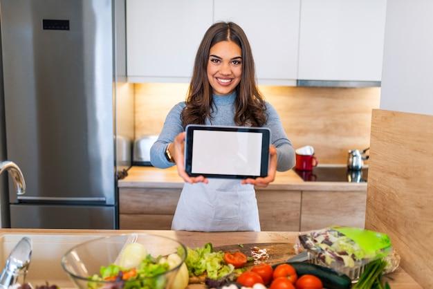 Giovane donna utilizzando un tablet pc per cucinare nella sua cucina