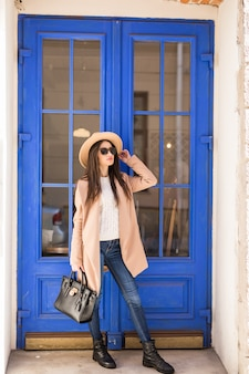 Giovane donna vestita casual in cappello cappotto luminoso e occhiali da sole è in piedi davanti alla porta blu