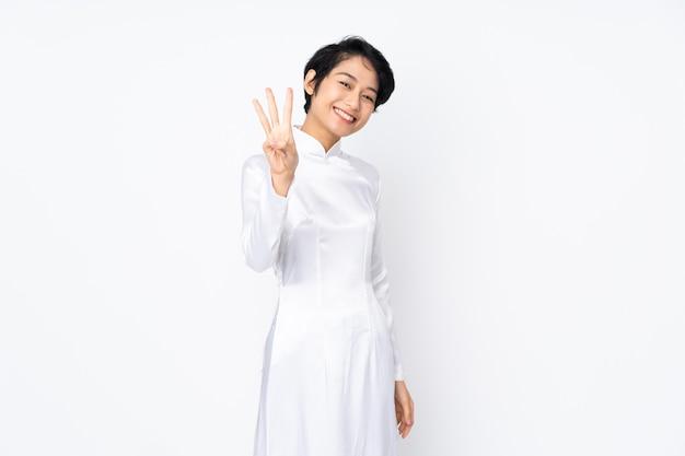 Giovane donna vietnamita con i capelli corti che indossa un abito tradizionale sul muro bianco felice e contando tre con le dita