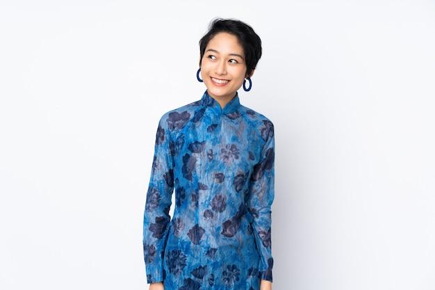 Giovane donna vietnamita con i capelli corti che indossa un abito tradizionale sul muro bianco pensando un'idea mentre guardando in alto
