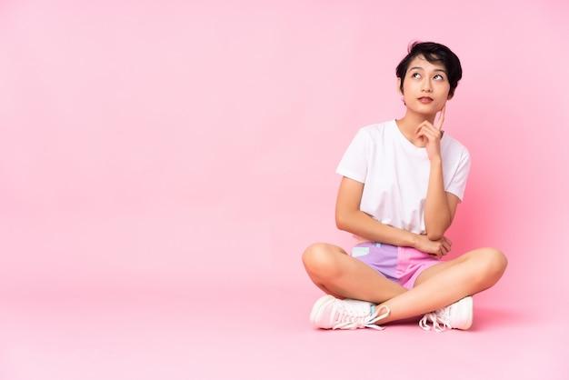 Giovane donna vietnamita con i capelli corti che si siede sul pavimento sopra il rosa isolato