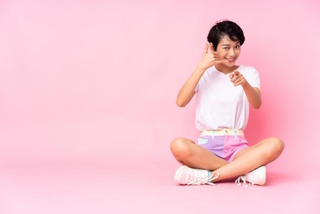 Giovane donna vietnamita con i capelli corti che si siede sul pavimento sopra la parete rosa isolata che fa gesto del telefono e che indica parte anteriore
