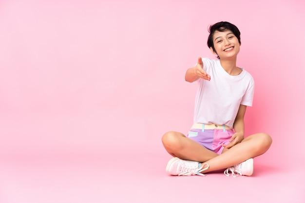 Giovane donna vietnamita con i capelli corti che si siede sul pavimento sopra la parete rosa isolata che stringe le mani per chiudere molto