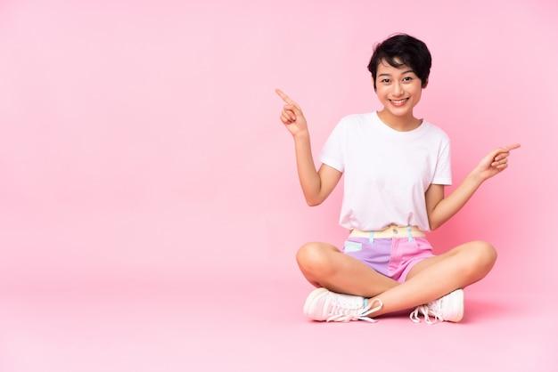 Giovane donna vietnamita con i capelli corti, seduta sul pavimento sopra il muro rosa che punta il dito ai lati e felice