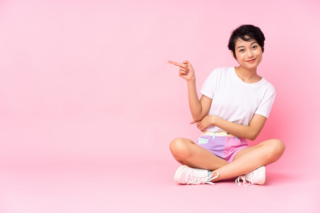 Giovane donna vietnamita con i capelli corti, seduta sul pavimento sul muro rosa che punta il dito verso il lato