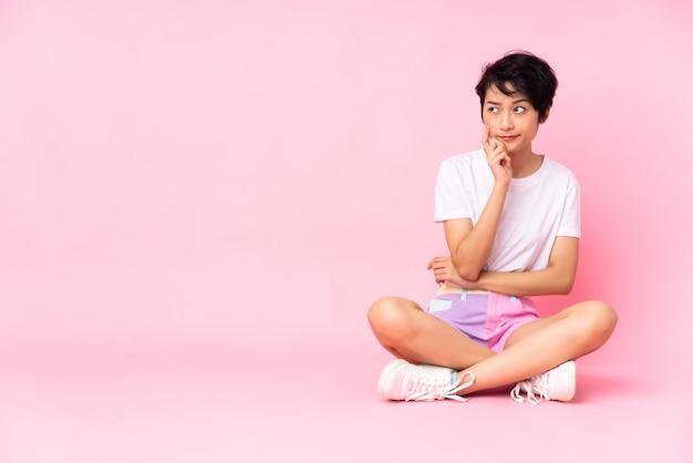 Giovane donna vietnamita con i capelli corti, seduta sul pavimento sul muro rosa con dubbi e con espressione del viso confuso