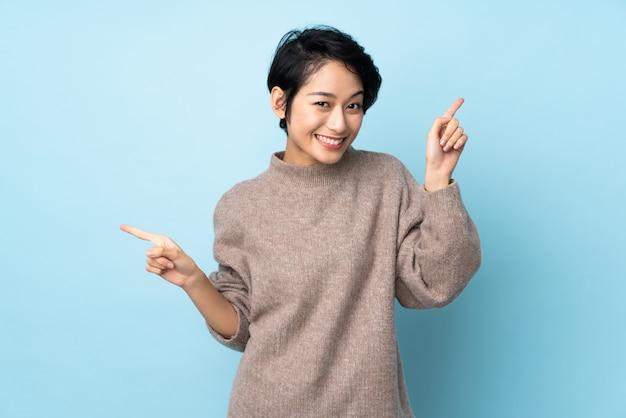 Giovane donna vietnamita con i capelli corti sopra il muro che punta il dito ai lati e felice
