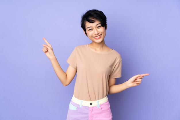 Giovane donna vietnamita con i capelli corti sopra il muro viola isolato che punta il dito ai lati e felice