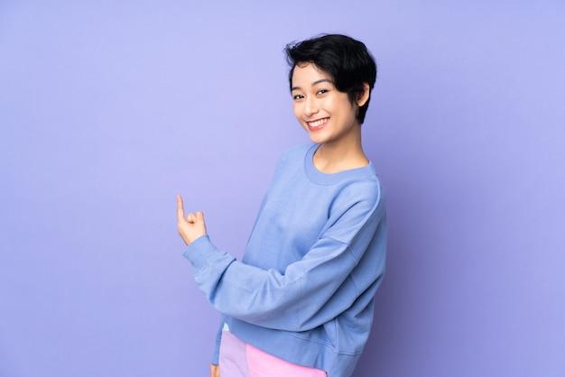 Giovane donna vietnamita con i capelli corti sopra la parete viola isolata che punta indietro