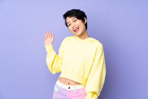 Giovane donna vietnamita con i capelli corti sopra la parete viola isolata che saluta con la mano con l'espressione felice