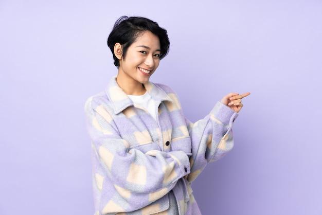 Giovane donna vietnamita con i capelli corti sul muro che punta il dito verso il lato