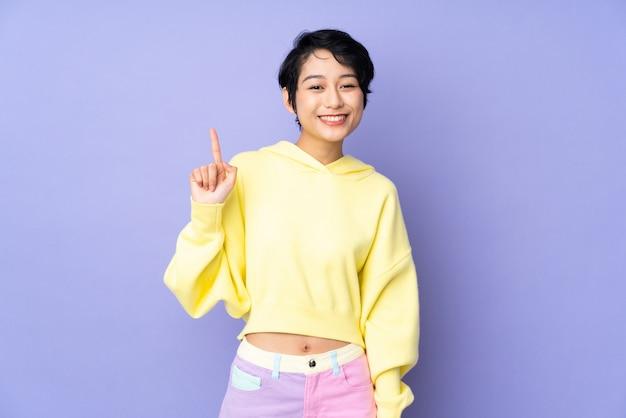 Giovane donna vietnamita con i capelli corti sul muro viola che mostra e sollevando un dito in segno del meglio