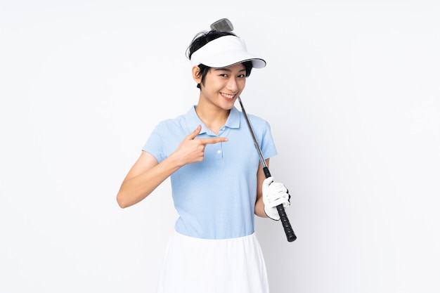 Giovane donna vietnamita del giocatore di golf sopra la parete bianca che gioca a golf e che indica il laterale
