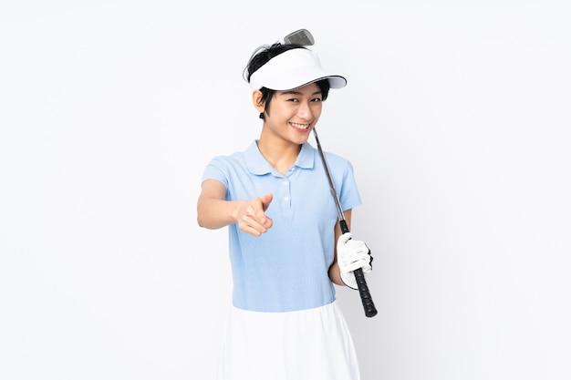 Giovane donna vietnamita del giocatore di golf sopra la parete bianca che gioca a golf e che indica la parte anteriore