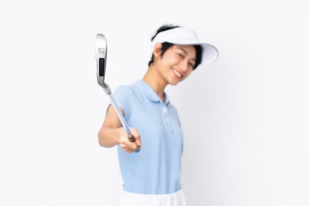 Giovane donna vietnamita del giocatore di golf sopra la parete bianca che gioca golf