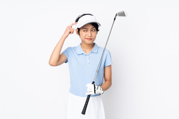 Giovane donna vietnamita del giocatore di golf sopra la parete bianca che ha dubbi e con l'espressione confusa del fronte