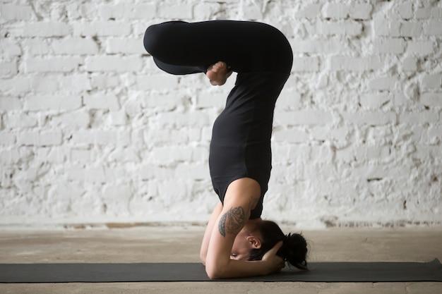 Giovane donna yogi attraente in posa headstand, backgr loft bianco