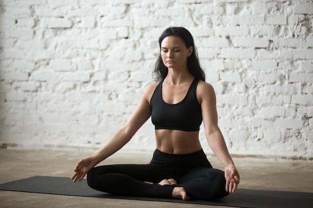 Giovane donna yogi attraente in posa mezzo loto, loft sfondo
