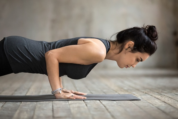 Giovane donna yogi facendo push up o stampa