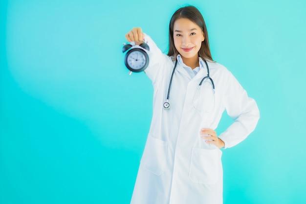 Giovane dottoressa asiatica con orologio o sveglia