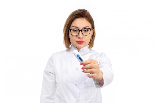Giovane dottoressa in bianco tuta medica tenendo la misura della temperatura sul bianco