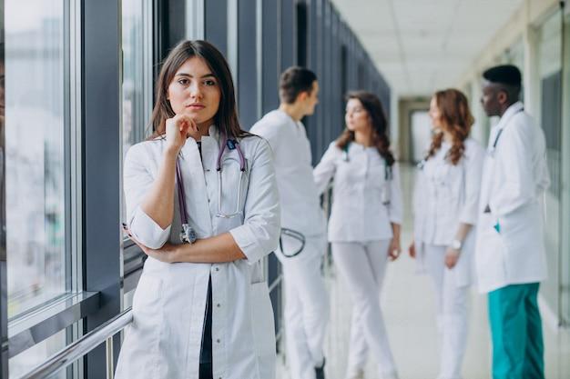 Giovane dottoressa in posa nel corridoio dell'ospedale