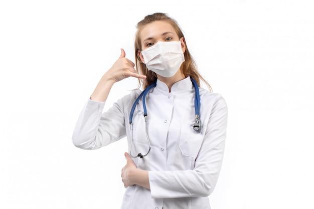 Giovane dottoressa in tuta medica bianca in maschera protettiva bianca stetoscopio in posa sul bianco