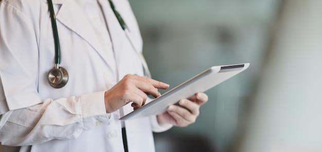 Giovane dottoressa riassume i grafici dei pazienti con tavoletta digitale