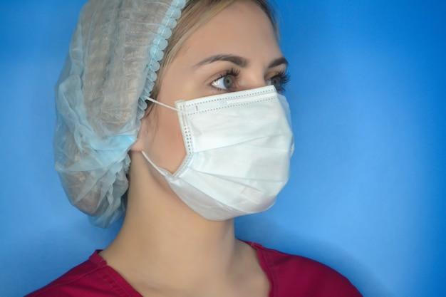 Giovane dottoressa su sfondo blu. concetto di assistenza sanitaria, medicina e pandemia. medico in un abito medico e maschera protettiva