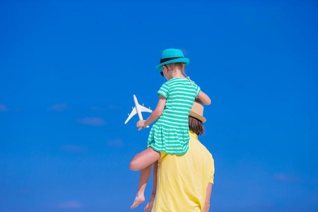 Giovane e bambina con la miniatura dell'aeroplano alla spiaggia