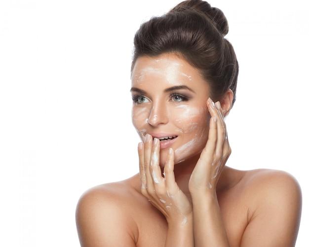 Giovane e bella donna che applica crema idratante sul viso