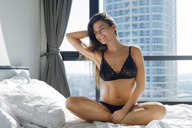 Giovane e bella donna che indossa lingerie nera, seduta sul letto