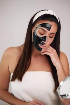 Giovane e bella donna con maschera peel-off nera sul viso dopo la doccia