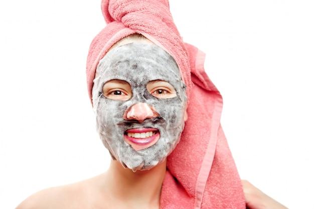 Giovane e bella donna con un asciugamano rosa in testa fa una maschera e sorride