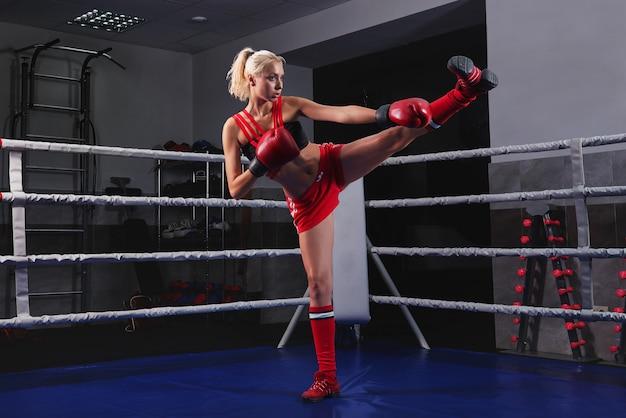 Giovane e bella donna forte e in forma allenamento boxe