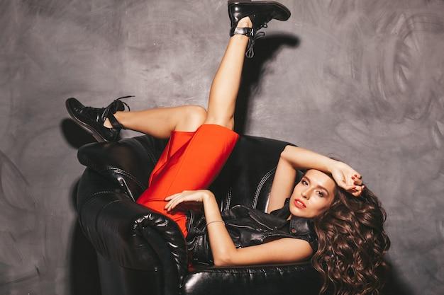 Giovane e bella donna in gonna rossa estiva alla moda e giacca di pelle nera.