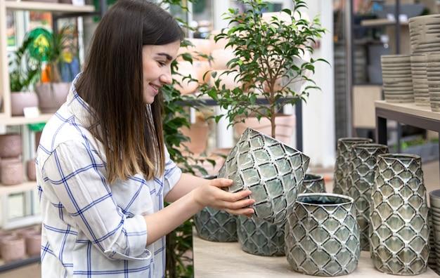 Giovane e bella donna sceglie un vaso di fiori in un negozio di fiori.