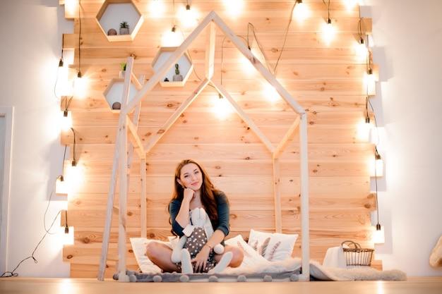 Giovane e bella donna seduta tra le luci della ghirlanda