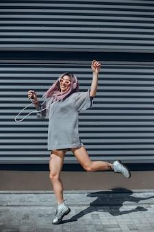 Giovane e bella ragazza usa uno smartphone per strada, navigando in internet e ascoltando musica