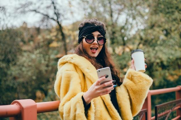 Giovane e bella ragazza usa uno smartphone per strada, navigando in internet e bevendo caffè