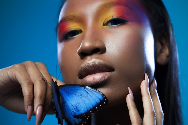 Giovane e bellissimo modello nero dall'aspetto esotico con farfalla blu brillante