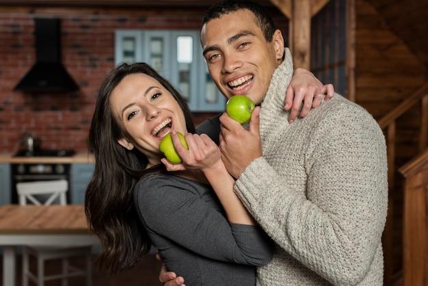 Giovane e donna che mangiano una mela