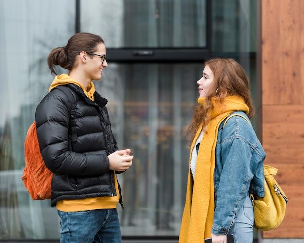 Giovane e donna che parlano l'un l'altro